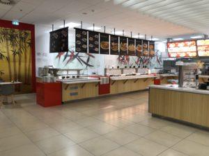 Realizace fast-foodu Panda ve Zlíně. Při této realizaci komerčního prostoru můžete vidět červené lakované MDF dílce v kombinaci s bambusovou dýhou a bílými corianovými deskami.