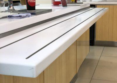 Realizace fast-foodu Panda ve Zlíně. Veškeré vodící a pracovní desky jsou vyrobeny z bílého umělého kamene - Corian.