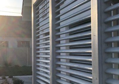 Moderní šedá pergola s pultovou střechou, bočními slunečními clonami, krytinou z polykarbonátu a antracitovými klempířskými prvky.